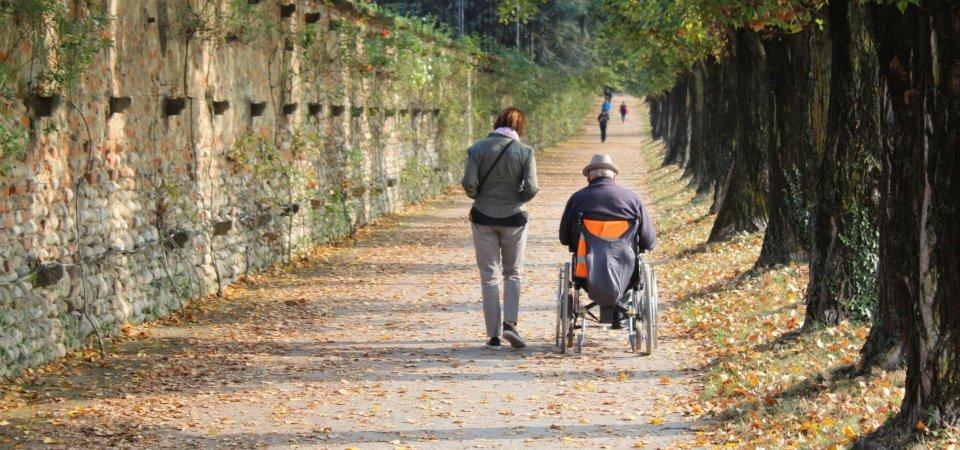Accompagnatrice con disabile nel parco in autunno